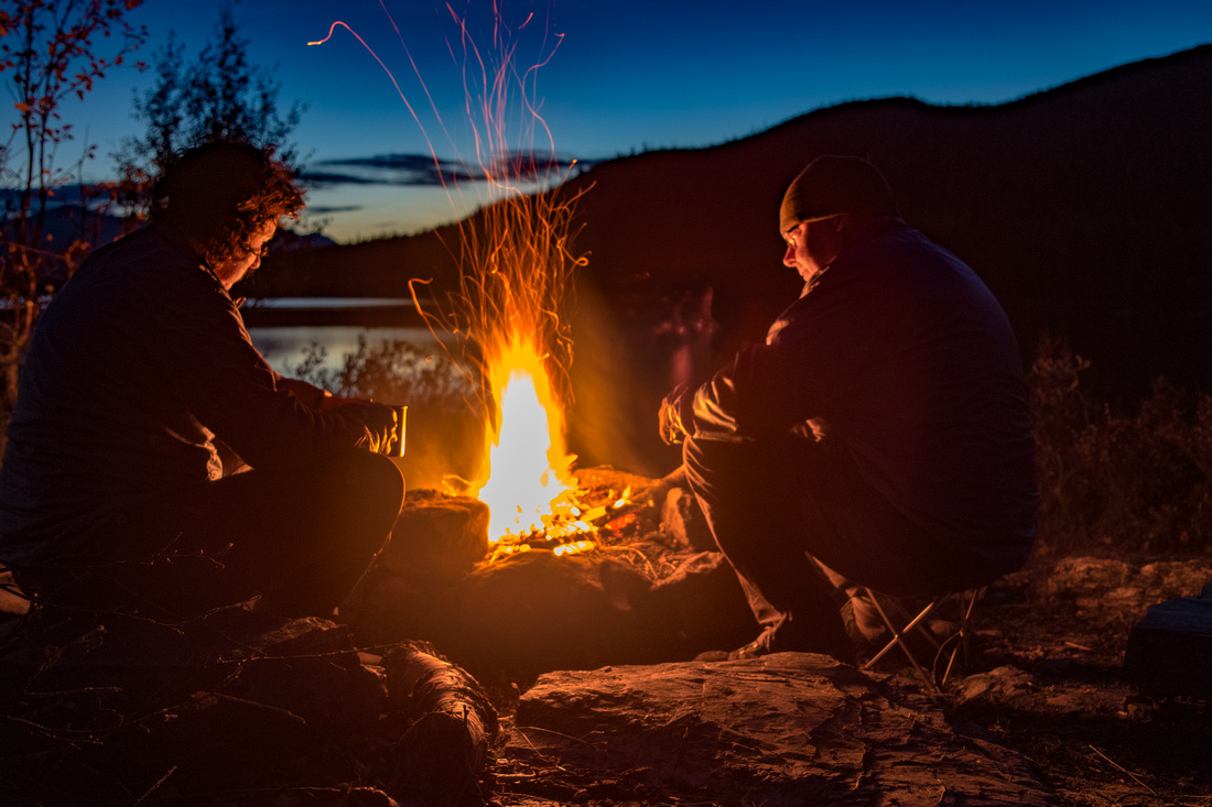 Campfire beside a lake in Arctic Sweden