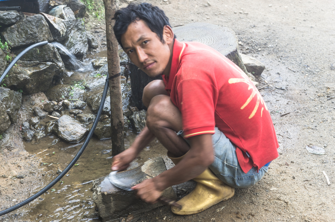 Sherpa villager sharpening a sickle
