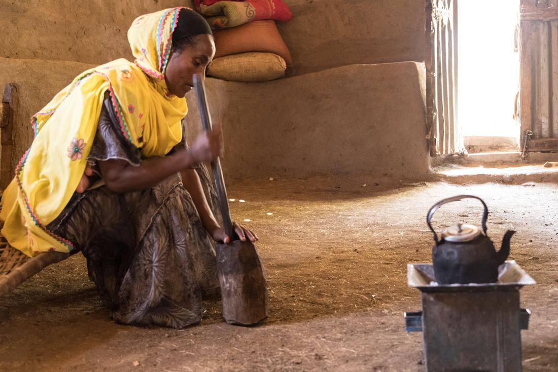 Grinding roasted coffee beans, Haweza Village