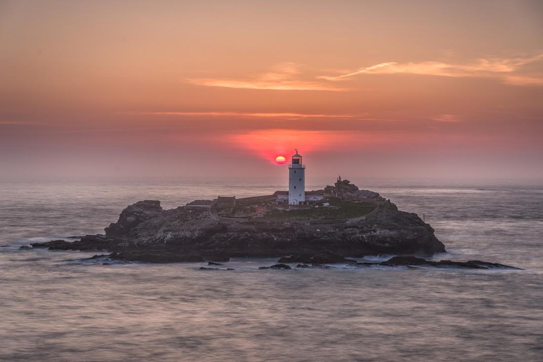 Sun setting behind Godrevy Lighthouse