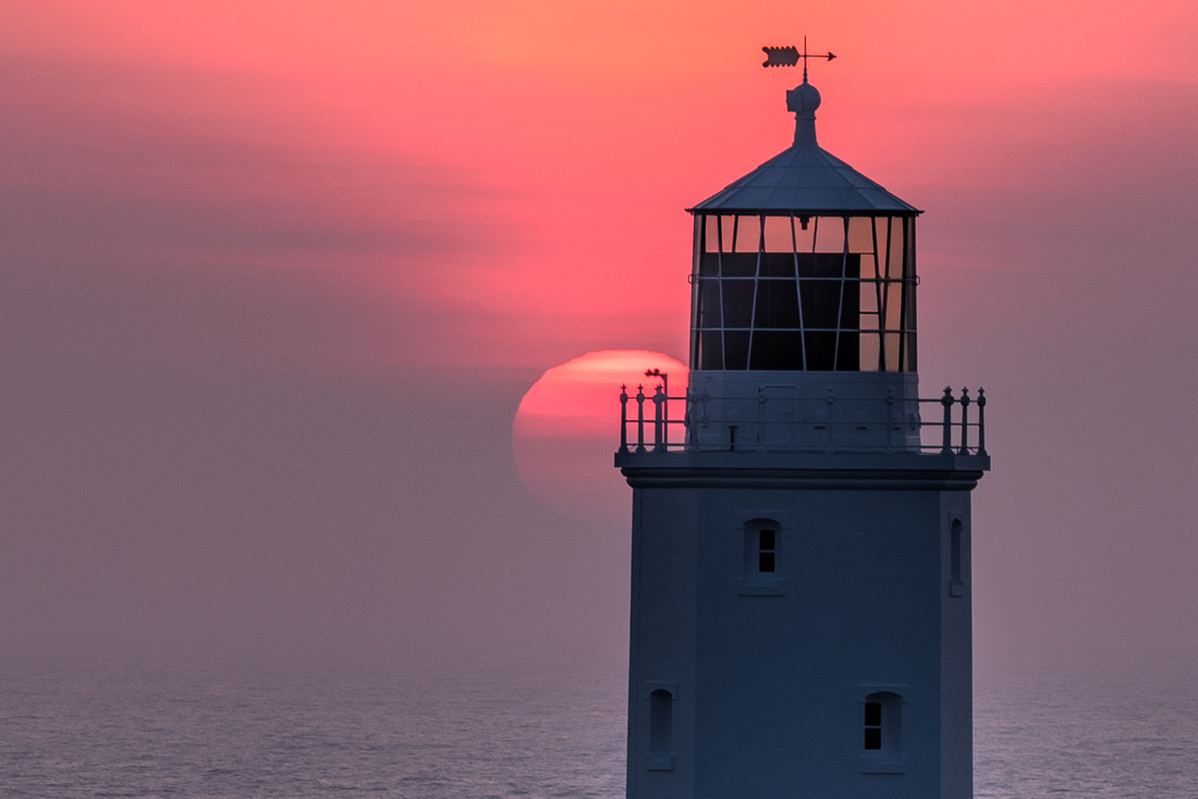 The red orb of the setting sun behind Godrevy Lighthouse