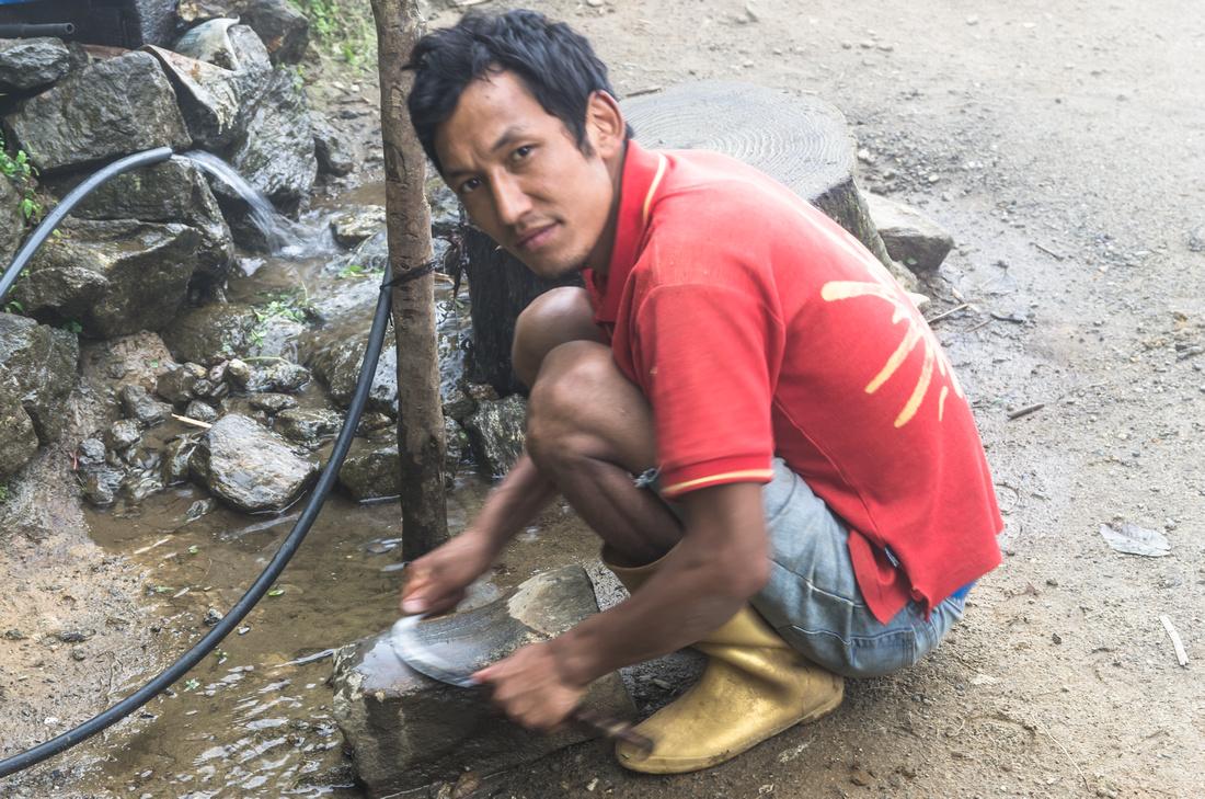 Sherpa villager sharpening a sickle